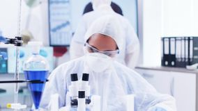 Female scientist in coverall equipment adjusting microscope in modern laboratory. Female scientist in coverall equipment writing notest and looking through stock video