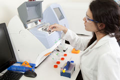 Female Scientist doing research. Female scientist using a DNA sequencer in a research lab Stock Photos