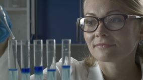 Female scientist dropping liquid into test tubes stock video footage