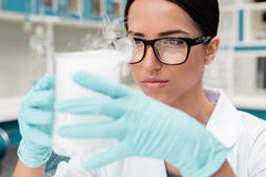 Female scientist in eyeglasses holding flask while making experiment in chemical lab Royalty Free Stock Images