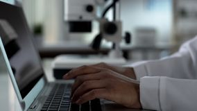 Female scientist hands typing on laptop, working on experimental research in lab. Stock photo stock image