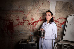 Female scientist holding an aluminum box in front of a blood spl Stock Photography