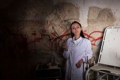 Female scientist holding large iron scissors in dungeon Stock Photo