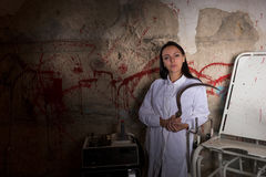 Female scientist holding large iron sickle in dungeon Stock Images