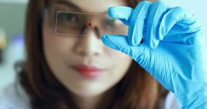 Female scientist holding sample glass in hand. stock video footage