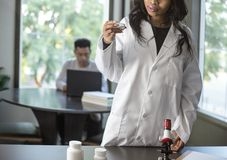 Med School Student and Female Scientist. Female scientist in a lab coat researching with her male coed med school student in a campus laboratory.  The women is Royalty Free Stock Photography