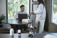 Med School Student and Female Scientist. Female scientist in a lab coat researching with her male coed med school student in a campus laboratory.  The women is Stock Image
