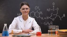 Female scientist in laboratory looking to camera, equipment standing on table. Stock footage stock video