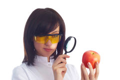 Female scientist looking at apple Stock Images