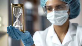 Female scientist looking at hourglass with sand flowing down, limited time stock photo