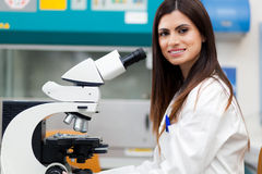 Female scientist looking through microscope Stock Image