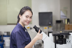 Female scientist looking in microscope Royalty Free Stock Photo