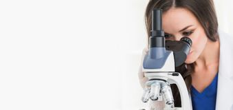 Female scientist with microscope. Female scientist working in a lab with microscope, isolated on white royalty free stock image