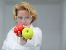 Female scientist offering natural food. Image of a female researcher offering a tomato and an apple to suggest the idea that healthy eating is recommended also Royalty Free Stock Images