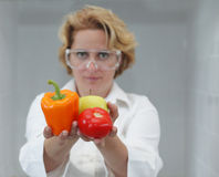 Female Scientist Offering Natural Food. Image of a female researcher offering a tomato and an apple to suggest the idea that healthy eating is recommended also Royalty Free Stock Photo