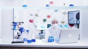 Female scientist in protection gear typing on computer. Reactive blue solution. Male researcher in the background stock footage