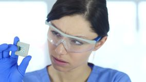 Female scientist in protective glasses looking at computer chip. 4k, high quality stock video footage