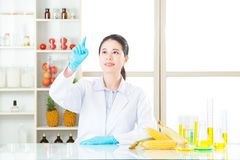 Female scientist research on touch screen for gmo food Royalty Free Stock Photo