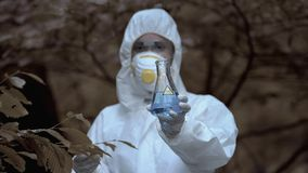 Free Female Scientist Showing Test Tube Radioactive Water Marked Poison, Biohazard Royalty Free Stock Images - 161864349