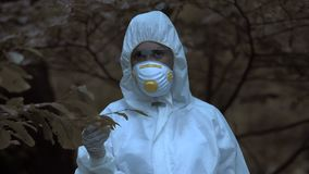 Female scientist showing test tube radioactive water marked poison, biohazard. Stock footage stock video