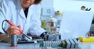 Female scientist soldering circuit board 4k stock video