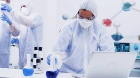 Female scientist stand up and typing on computer in a modern chemistry laboratory dressed up in coverall equipment. Smoking blue liquid with reagent stock video