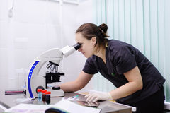 Female scientist studying new substance or virus in microscope. Portrait of young female scientist studying new substance or virus in microscope Stock Photo