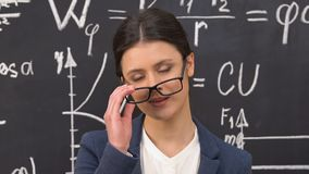 Female scientist taking off eyeglasses looking at camera, formulas on blackboard. Stock footage stock video footage