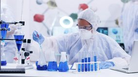 Female scientist taking samples of blue liquid from different test tubes using a pipette. Scientist searching for the right formula stock footage