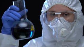 Female scientist in uniform showing biohazardous liquid in flask, chemical lab