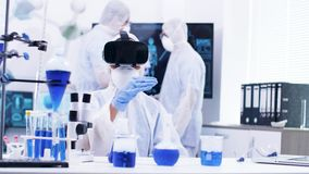 Female scientist using modern technology in research laboratory. Femakle scientist with virtual reality headset. Test tubes with blue liquid stock footage