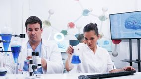 Female scientist in white coat and her assistant working with in modern lab research. Assistant helping female scientist with research. Smoking blue liquid stock footage