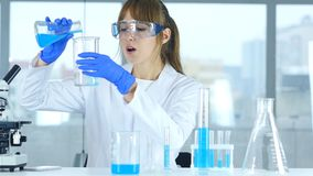 Female Scientist Working in Laboratory, Pouring Chemical Solution in Test Tube. 4k , high quality Stock Photo