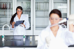 Female scientist writing on a clipboard Royalty Free Stock Images