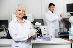 Female Scientist Writing On Clipboard In. Portrait of senior female scientist writing on clipboard with colleague working in background at laboratory Stock Images
