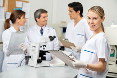 Female Scientist Writing On Clipboard In. Portrait of young female scientist writing on clipboard with colleagues in background at laboratory Royalty Free Stock Photos