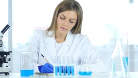 Female Scientist Writing Details, Result of Research in Laboratory royalty free stock image