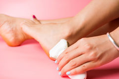 Female scrubbing hard skin from feet Stock Photos