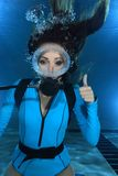 Female scuba diver hand signal. Female scuba diver with lycra suit show hand signal underwater in the pool Royalty Free Stock Photography