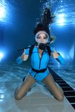 Female scuba diver hand signal. Female scuba diver with lycra suit show hand signal underwater in the pool Royalty Free Stock Photos