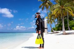 Female scuba diver stands on a tropical beach stock images