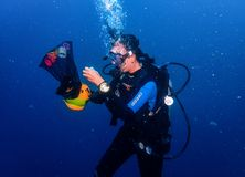 Female scuba diver underwater performing a dexterity exercise royalty free stock photos