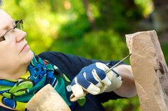 Female sculptor. Female stonemason at work in the garden Royalty Free Stock Image