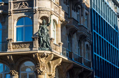 Female sculpture on the corner of building. Female monument stands on the corner of home Royalty Free Stock Image