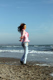 Female sea. A pretty girl on a sunny day walking on the beach Royalty Free Stock Image