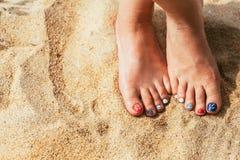 Female sea style pedicured feet on summer shore sand on sunny da Stock Images