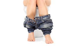 Female seated at a toilet with her pants down Stock Photos