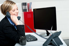 Female secretary answering bosses call Royalty Free Stock Image