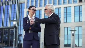 Female secretary apologizing to elderly boss for being late, work discipline royalty free stock image