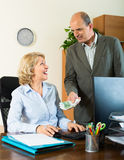 Female secretary receiving from boss salary Stock Photos